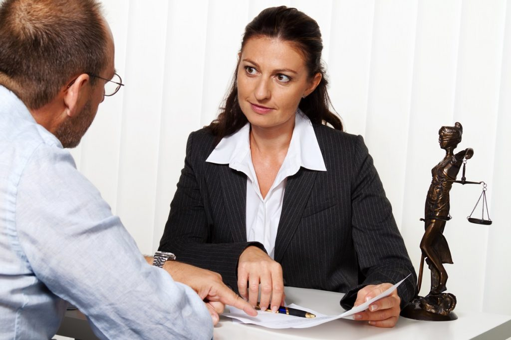 Man consulting a young wage garnishment attorney